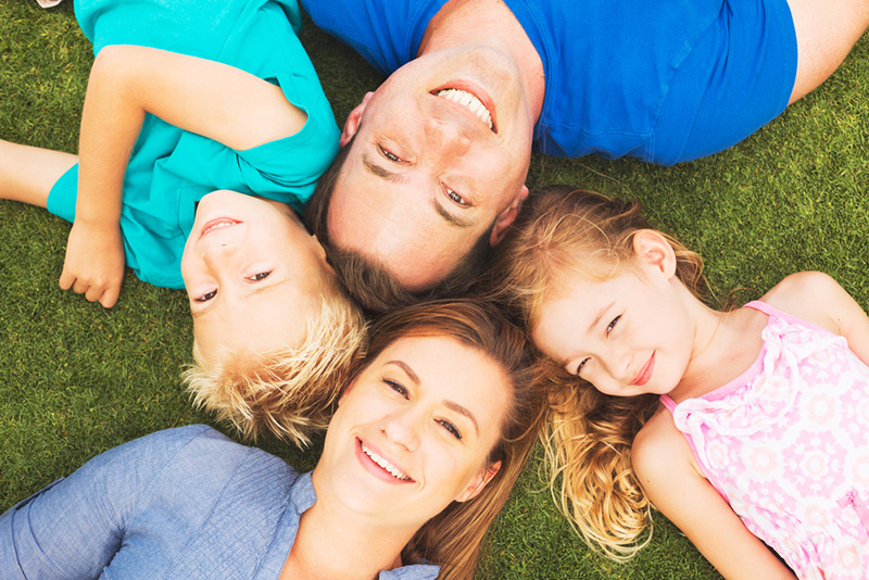 FamilFamily of mother, father, son and daughter lying on the grass after visiting their after visiting Stewart Family Dentist