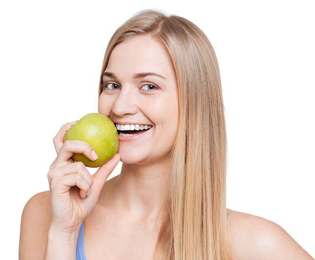 Smiling woman bites into an apple