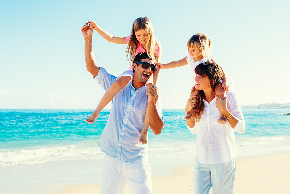 Mother and father supporting one of each of their children on their sholders at the beach